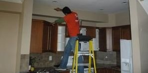 Technician Removing Water Damage Off Of Ceiling